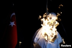 FILE - Supporters of Turkish President Tayyip Erdogan burn an effigy of U.S.-based cleric Fethullah Gulen hanged by a noose during a pro-government demonstration on Taksim Square in Istanbul, Turkey, July 18, 2016.
