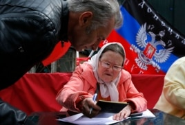 A woman checks documents of a Ukrainian man before issuing him a paper ballot in Moscow, Russia, May 11, 2014. Many Ukrainians living in Moscow came to vote as well.