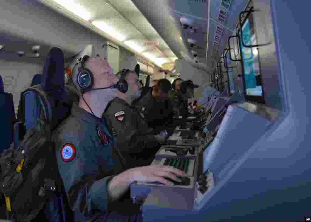 In this photo provided by the U.S. Navy, crew members on board an aircraft P-8A Poseidon assist in the search and rescue operations for Malaysia Airlines flight MH370 in the Indian Ocean,  March 16, 2014.