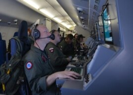 In this photo provided by the U.S. Navy, crew members on board an aircraft P-8A Poseidon assist in search and rescue operations for Malaysia Airlines flight MH370 in the Indian Ocean, March 16, 2014.