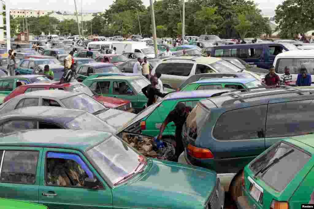 Um homem coloca água no radiador do carro enquanto espera nas filas incríveis para abastecer o carro. Abuja, Nigéria 25 de Maio 2015