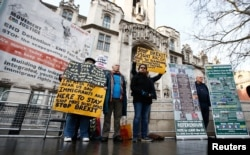 Pro and anti-Brexit protesters stand outside the Supreme Court on the third day of the challenge against a court ruling that Theresa May's government requires parliamentary approval to start the process of leaving the European Union, in Parliament Square,