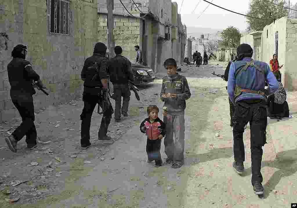 Syrian boys watch Free Syrian Army fighters move through a neighborhood in Damascus. (AP)
