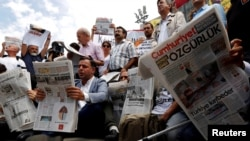 FILE PHOTO: Press freedom activists read opposition newspaper Cumhuriyet during a demonstration in solidarity with the jailed members of the newspaper outside a courthouse, in Istanbul, Turkey, July 28, 2017. REUTERS/Murad Sezer/File Photo