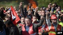 Des membres des syndicats français font grève près de la raffinerie de Total basée à Donges, à l'ouest de la France, pour protester contre la loi sur le travail le 27 mai 2016.