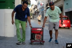 FILE - Men push a generator along Fortaleza street, one month after Hurricane Maria, in San Juan, Puerto Rico, Oct. 20, 2017.