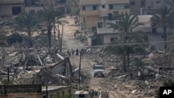 Egyptian army forces patrol amid the debris of houses destroyed by the army in the Egyptian border town of Rafah, as seen from the Palestinian side of Rafah in the southern Gaza Strip, Nov. 4, 2014.