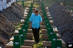 FILE - A Bosnian man walks among graves during a funeral ceremony for the 136 victims at the Potocari memorial complex near Srebrenica, 150 kilometers (94 miles) northeast of Sarajevo, Bosnia and Herzegovina, July 11, 2015.