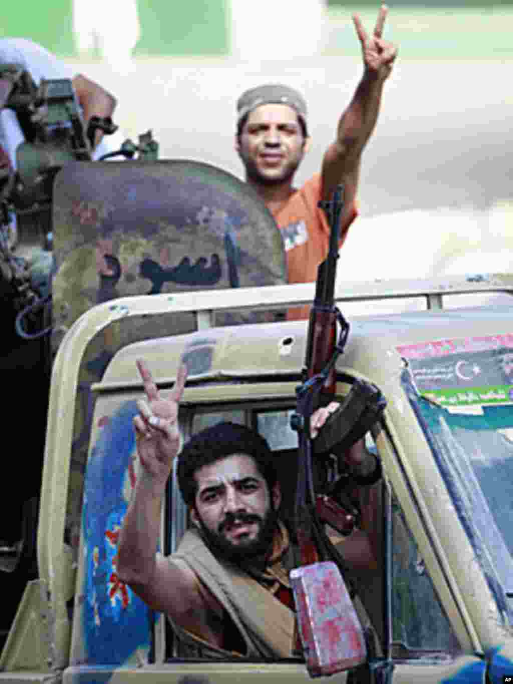 Libyan rebel fighters celebrate as they drive through Tripoli's Qarqarsh district, August 22, 2011. (Reuters)