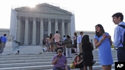 People line up in front of the Supreme Court in Washington, Jun. 24, 2013, before it opened for its last scheduled session.