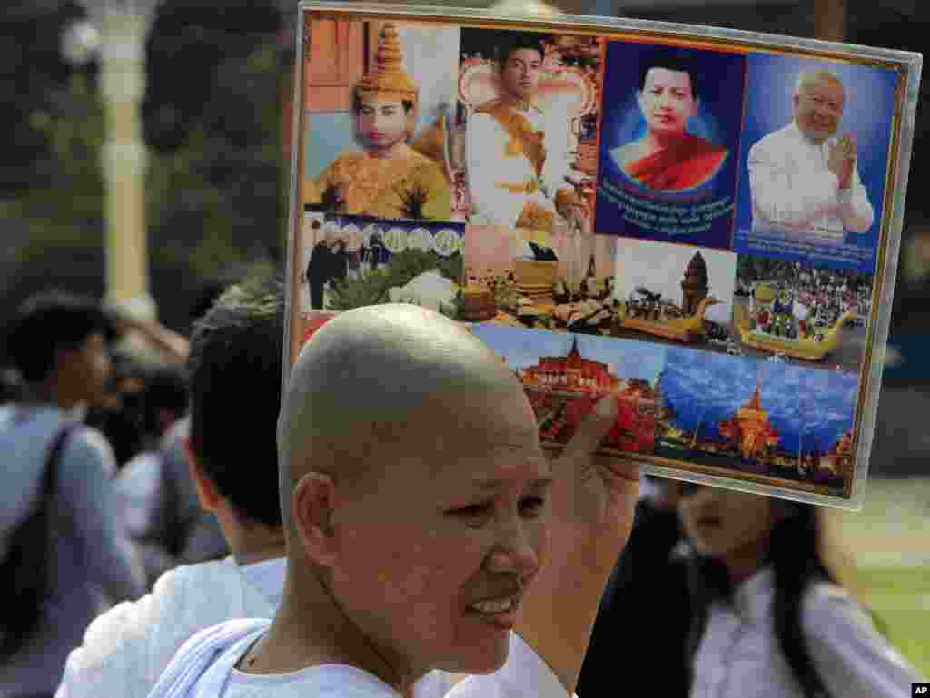 A Buddhist nun holds the portraits of Cambodia's late King Norodom Sihanouk Thursday, Jan. 31, 2013, in Phnom Penh, Cambodia. The body of Sihanouk who died on Oct. 15, 2012 at age 89, is scheduled to be cremated on Feb. 4, 2013. (AP Photo/Heng Sinith)