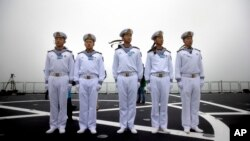 Chinese sailors stand on the deck of the naval training ship Qi Jiguang during a naval parade to commemorate the 70th anniversary of the founding of China's PLA Navy in the sea near Qingdao in eastern China's Shandong province, Tuesday, April 23, 2019.