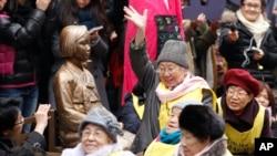 在二战期间曾被迫充当日军慰安妇的韩国妇女在日本驻首尔大使馆前的一座韩国前慰安妇的雕塑前集会,要求日本政府正式道歉与赔偿。(资料照片)