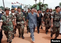 Cambodian Prime Minister Hun Sen, pictured here with his bodyguards in 1997, is one of the world's longest serving leaders. REUTERS/Stringer