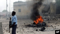 A Somali government policeman stands by a still burning car shortly after it exploded in Somalia's capital, Mogadishu, December 6, 2011.