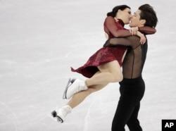加拿大的斯科特·莫伊尔与特萨·维楚在平昌冬奥会江陵冰场的花样滑冰团体赛中进行冰上舞蹈自由舞动作。(2018年2月12日)