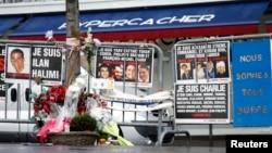 6일 프랑스 파리의 한 상점 앞에 지난해 '샤를리에브도' 사옥 총격으로 사망한 희생자들을 애도하는 화환과 메세지가 놓여있다.