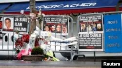 Karangan bunga dan pesan-pesan untuk mengenang para korban penembakan setahun yang lalu, terlihat di depan supermarket halal Hyper Cacher di Porte de Vincennes, Paris, Perancis (6/1).