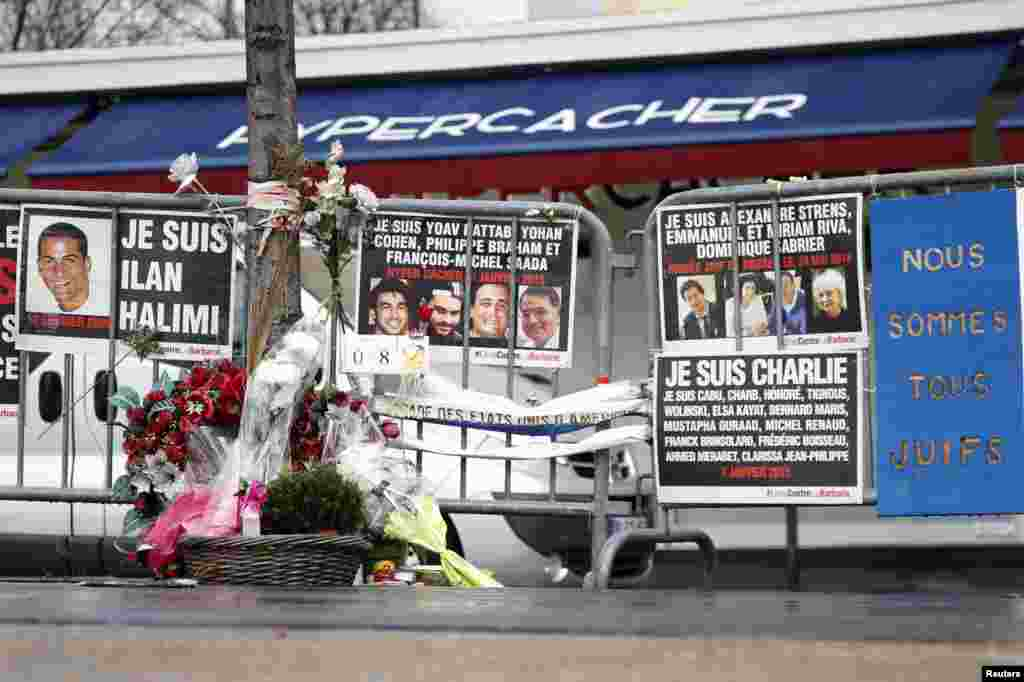 Flowers and messages in tribute to the victims of last year's January attacks are seen in front of the Hyper Cacher kosher supermarket at the Porte de Vincennes in Paris, France, Jan. 6, 2016.