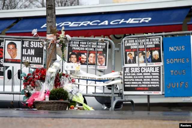 FILE - Flowers and messages in tribute to the victims of last year's January attacks are seen in front of the Hyper Cacher kosher supermarket at the Porte de Vincennes in Paris, France, Jan. 6, 2016.
