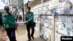 Police officers carry ballot boxes to a polling center in Dhaka for parliamentary elections, Jan. 4, 2014.