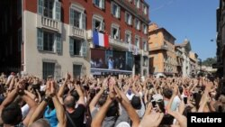 France soccer team goalkeeper Hugo Lloris surrounded by his wife Marine, relatives and Christian Estrosi, Mayor of Nice, waves to the crowd from a balcony at the city hall in Nice, after their victory in the 2018 Russia Soccer World Cup, in Nice, France,