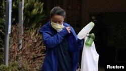 Seorang pekerja melepas masker setelah meninggalkan fasilitas perawatan Life Care Center of Kirkland yang terkait dengan beberapa kasus positif infeksi virus corona, di Kirkland, Washington, 6 Maret 2020.
