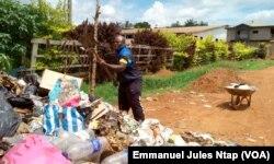 Stéphane ramasse les ordures sans protection pour dégager la voie publique obstrueés par les ordures ménagères au quartier Tropicana, à Yaoundé, au Cameroun, le 23 mai 2017. (VOA/Emmanuel Jules Ntap)