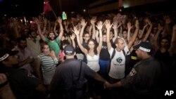 Para aktivis Israel mengangkat tangan mereka saat berunjuk rasa di Tel Aviv (24/6). Pihak berwenang telah menangkap sedikitnya 85 orang pasca bentrokan demonstran dan polisi dan pengrusakan di bank-bank di ibukota Israel ini.