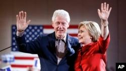 Kandidat capres Partai Demokrat Hillary Clinton, kanan, melambai dari panggung bersama suaminya mantan Presiden Bill Clinton di pemilihan pendahuluan kaukus Demokrat di Las Vegas, 20 Februari 2016.