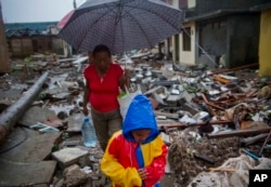 A boy amd a woman walk next to remains of houses destroyed by Hurricane Matthew in Baracoa, Cuba, Oct. 5, 2016.