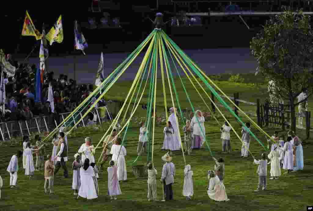 Para aktor membuat formasi lingkaran dalam Upacara Pembukaan Olimpiade 2012 di London (27/7).