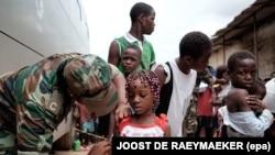 Un militaire angolais administre un vaccin de fièvre jaune à un enfant au marché 'quilometro 30', Luanda, Angola, 16 février 2016. epa/ JOOST dE Raeymaeker