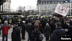 """Counter-demonstrators gather to show their disapproval of a movement calling itself """"The People's Demonstration"""", which held a meeting and demonstration at Norrmalmstorg square in Stockholm, Sweden, Jan.30, 2016."""