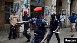 Un policier fait un geste au parti d'opposition qui manifeste avant l'arrivée de Barack Obama, à Dakar, le 25 juin 2013.