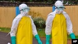 Petugas kesehatan Liberia mengenakan pakaian pelindung untuk memindahkan jenazah bekas pasien ebola di Monrovia (16/8).