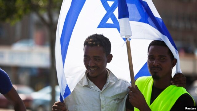 FILE - African migrants from Eritrea hold an Israeli flag during a protest near the Ministry of Defense in Tel Aviv, October 18, 2012.
