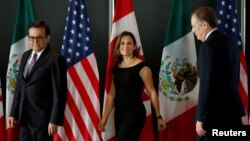 FILE - From left, Mexico's Economy Minister Ildefonso Guajardo, Canada's Foreign Minister Chrystia Freeland and U.S. Trade Representative Robert Lighthizer arrive for a meeting during the third round of NAFTA talks involving the United States, Mexico and Canada in Ottawa, Ontario, Sept. 27, 2017.