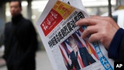 "A man reads a newspaper with the headline of ""U.S. President-elect Donald Trump delivers a mighty shock to America"" at a news stand in Beijing, Thursday, Nov. 10, 2016."