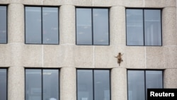A raccoon scurries up the side of the UBS Plaza building in St. Paul, Minnesota, U.S., June 12, 2018, in this image obtained from social media.