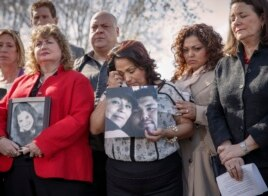 Rosie Cortinas (C) holds a photo of her son who was killed Oct. 18, 2013 while driving a Chevy Cobalt, joins other families whose loved ones died behind the wheel defective GM vehicles, during a news conference in Washington, April 1, 2014.