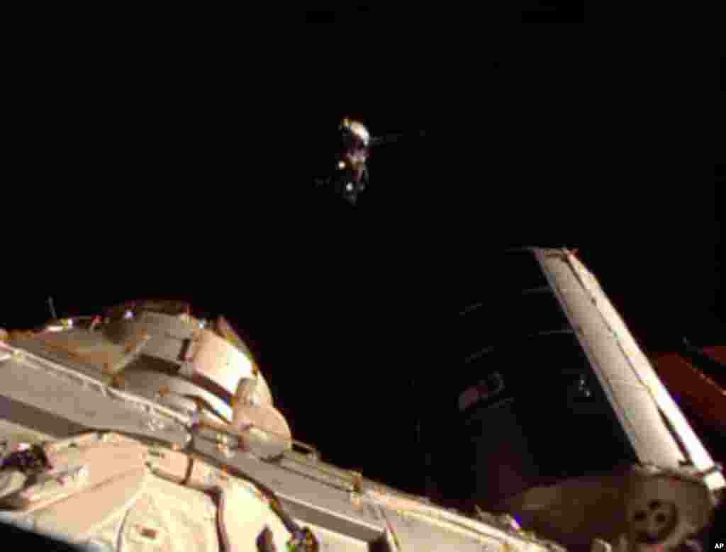 This image taken from video provided by NASA shows the Soyuz carrying three new Expedition 36 crew members, top, approaching the International Space Station, May 29, 2013.