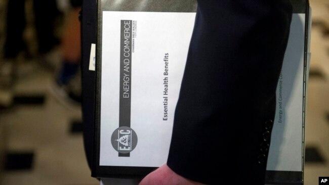 """El presidente del Comité de Energía y Comercio de la Cámara de Representantes, Greg Walden, uno de los defensores de la legislación republicana en materia de salud, lleva una carpeta titulada """"Beneficios Esenciales de Salud"""" al salir de la oficina del Capitol Hill, este 24 de marzo, 2017."""