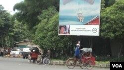 """Salah satu papan reklame yang menampilkan iklan rokok di dekat taman kota Banjarsari, Solo, 9 Januari 2014 (VOA/Yudha Satriawan). Pemkot Solo mulai menghilangkan papan reklame rokok di seluruh wilayah kota tersebut mulai tahun ini, untuk mewujudkan """"Kota Layak Anak 2015""""."""