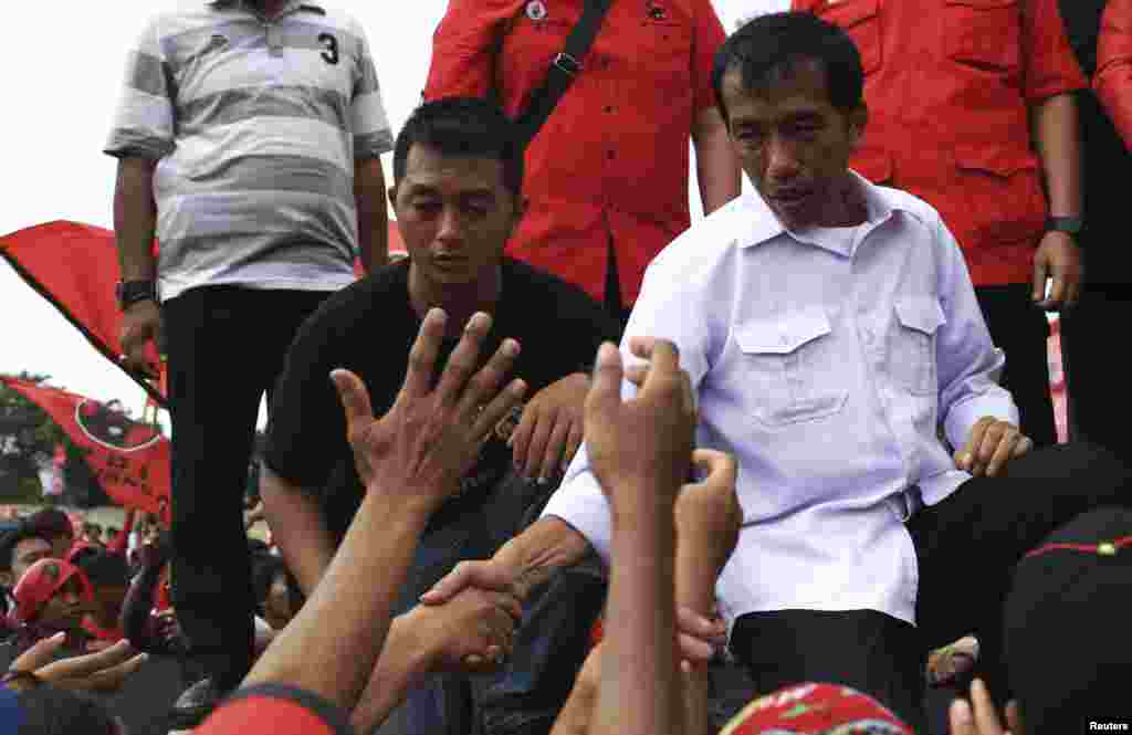 Jakarta governor and presidential candidate Joko Widodo greets his supporters during a PDI-P party campaign in Jakarta, March 16, 2014.