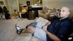 Sersan John Borders (kanan), veteran yang terluka di Irak, di ruang keluarganya (foto: dok).