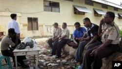 Polisi berjaga di luar stadion di Nabire, Papua, tempat lebih dari selusin orang tewas karena terinjak-injak menyusul kerusuhan dalam pertandingan tinju (15/7). (Foto: AP)
