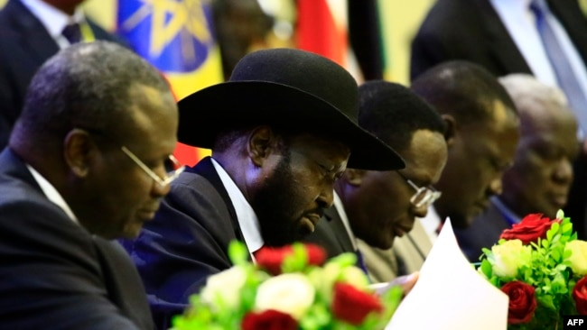 FILE - South Sudan President Salva Kiir signs a final power-sharing deal between South Sudanese arch-foes, in Khartoum, Aug. 5, 2018. Formation of a transitional government is expected to miss its May 12 deadline.