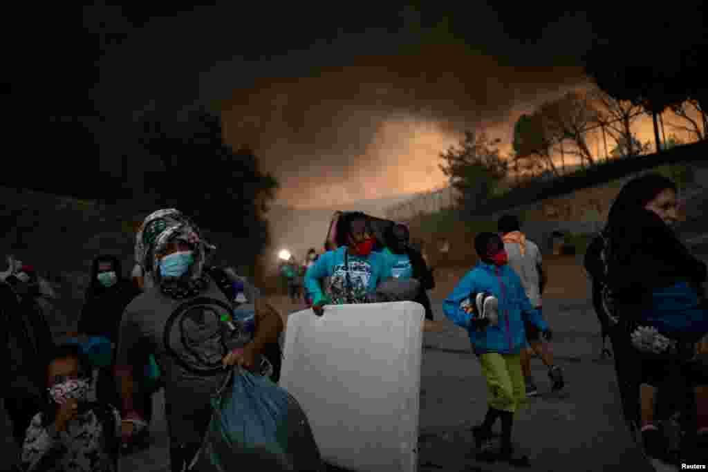موریہ کیمپ میں آگ لگنے کے بعد پناہ گزین اپنا بچا کچا سامان سمیٹ کر محفوظ مقام تلاش کر رہے ہیں۔