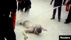 Policemen put out fire on a self-immolation victim at Ngapa County, Ngapa Tibetan and Qiang Autonomous Prefecture in Sichuan Province in this still image taken from a March 16, 2012 video footage and released to Reuters on December 25, 2012. Ngapa, a quie